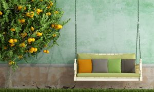 Vintage wooden swing in the garden of an old house in spring