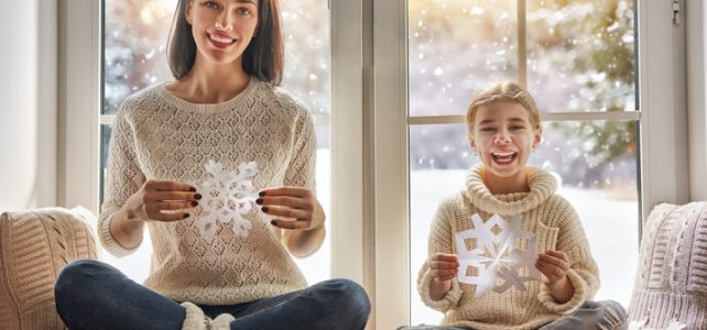 making paper snowflakes for decoration windows. Mother and child creating decorations.