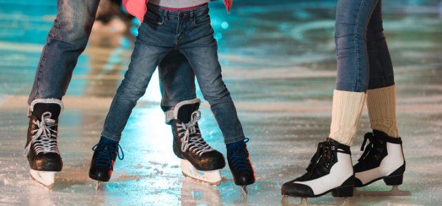 family in skates skating together on rink
