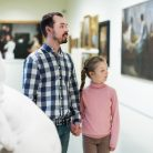 Glad young father and little daughter looking at expositions in museum